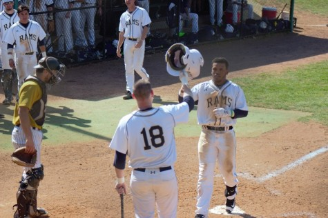 Tre Porter celebrates with #18 Christian Hamel after a home run against West Virginia State