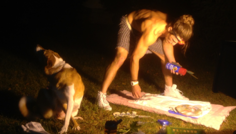 Chad A., with the company of his dog, takes advantage of a quiet night in Shepherdstown to create custom clothing on the lawn of Reynolds Hall.