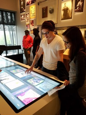Shepherd students James Walker and Megan Murray use an interactive display to set the playlist that plays over the musical exhibit.