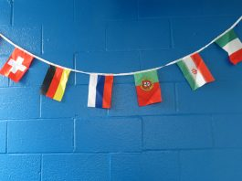 Different countries flags hanging on a wall.