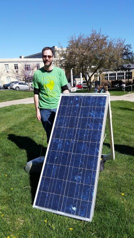 Dr. Jeffrey Groff stands beside a photovoltaic panel he set up to play radio and charge people's electronics.